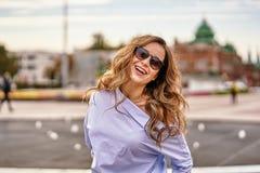Jeune femme heureuse avec de longs cheveux bruns dans des lunettes de soleil, promenades bleues de chemise par la vieille ville photos libres de droits