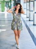 Jeune femme heureuse avec des yeux bleus souriant dehors Robe de port de fleur de fille à l'arrière-plan urbain image stock
