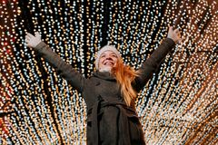 Jeune femme heureuse avec la lumière de Noël photographie stock