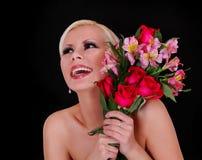 Jeune femme heureuse avec le bouquet des roses rouges et des iris roses au-dessus du fond noir Image stock
