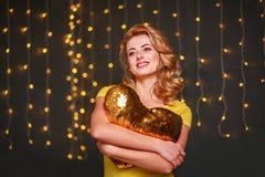 Jeune femme heureuse avec le coeur sur le fond de fête de lumières photos libres de droits