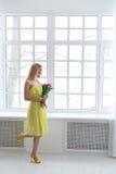 Jeune femme heureuse avec le groupe de tulipe dans la robe jaune Photos libres de droits