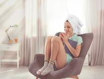 Jeune femme heureuse avec le livre et la tasse de café aromatique dans le fauteuil à la maison photo libre de droits
