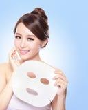 Jeune femme heureuse avec le masque de massage facial de tissu Photo libre de droits