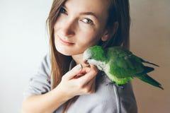 Jeune femme heureuse avec le perroquet se reposant sur son épaule Photo stock