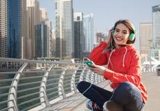 Jeune femme heureuse avec le smartphone et les écouteurs Photo libre de droits