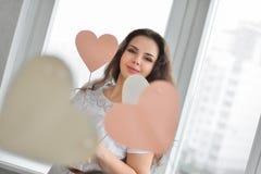 Jeune femme heureuse avec le symbole d'amour de coeur Photographie stock