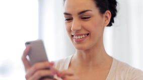 Jeune femme heureuse avec les accolades et le smartphone banque de vidéos