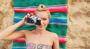 Jeune femme heureuse avec les détails colorés se trouvant sur la plage et le t image libre de droits