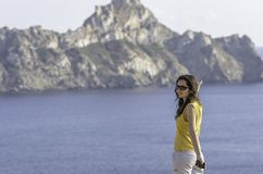 Jeune femme heureuse avec les mains augmentées et regarder la mer Photo libre de droits
