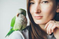 Jeune femme heureuse avec les yeux verts et le perroquet vert se reposant sur son épaule Photo stock
