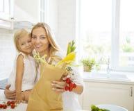 Jeune femme heureuse avec sa fille faisant cuire ensemble Photographie stock libre de droits