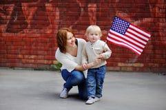 Jeune femme heureuse avec son fils d'enfant en bas âge tenant le drapeau américain Photos stock