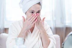 Jeune femme heureuse avec une serviette sur sa tête regardant sa peau dans un miroir Hygiène et entretenir opportuns la peau photos libres de droits
