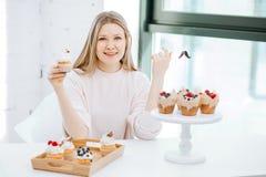 Jeune femme heureuse ayant des petits gâteaux se reposant près de la fenêtre photographie stock