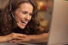 Jeune femme heureuse ayant la causerie visuelle de Noël sur l'ordinateur portable Photographie stock libre de droits