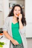 Jeune femme heureuse ayant un casse-croûte sain tout en faisant cuire photo stock