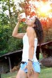 Jeune femme heureuse buvant la boisson froide et ayant l'amusement dehors à la forêt Photos stock