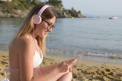 Jeune femme heureuse choisissant des chansons sur la plage photos stock