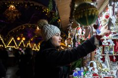 Jeune femme heureuse choisissant la décoration de Noël au marché photo stock