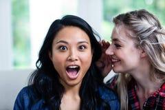 Jeune femme heureuse chuchotant à l'ami féminin Photographie stock libre de droits
