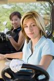 Jeune femme heureuse conduisant le chariot de golf Photo stock