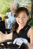 Jeune femme heureuse conduisant le chariot de golf Photographie stock libre de droits