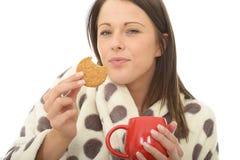 Jeune femme heureuse confortable décontractée attirante mangeant des biscuits avec le thé Photo stock
