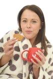 Jeune femme heureuse confortable décontractée attirante mangeant des biscuits et buvant du thé Image stock