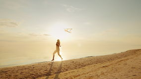 Jeune femme heureuse courant avec un cerf-volant banque de vidéos