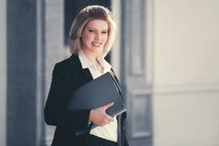 Jeune femme heureuse d'affaires avec le dossier à l'immeuble de bureaux images stock