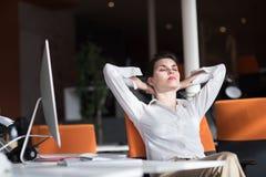 Jeune femme heureuse d'affaires détendant et obtenant l'insiration Image libre de droits