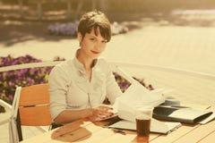 Jeune femme heureuse d'affaires de mode travaillant au café de trottoir photo stock