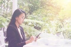 Jeune femme heureuse d'affaires s'asseyant au café urbain avec du café et à l'aide de son téléphone intelligent Photo libre de droits