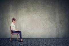 Jeune femme heureuse d'affaires s'asseyant sur une chaise utilisant son ordinateur portable photos libres de droits
