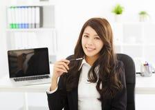 Jeune femme heureuse d'affaires travaillant dans le bureau Photos stock