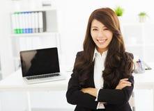 Jeune femme heureuse d'affaires travaillant dans le bureau Image stock