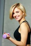 Jeune femme heureuse d'ajustement faisant la séance d'entraînement avec l'haltère Photographie stock
