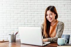 Jeune femme heureuse d'indépendant travaillant sur l'ordinateur portable d'ordinateur dans confortable photo stock