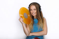 Jeune femme heureuse dans de grands écouteurs noirs du DJ de professionnel détenant le disque vinyle coloré jaune à la mode posan Image stock
