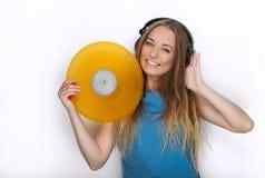 Jeune femme heureuse dans de grands écouteurs noirs du DJ de professionnel détenant le disque vinyle coloré jaune à la mode posan Photographie stock libre de droits