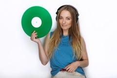 Jeune femme heureuse dans de grands écouteurs noirs du DJ de professionnel détenant le disque vinyle coloré vert à la mode posant Photos stock