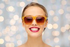 Jeune femme heureuse dans des lunettes de soleil avec le rouge à lèvres rose Image stock