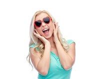 Jeune femme heureuse dans des lunettes de soleil de forme de coeur Image libre de droits