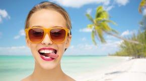 Jeune femme heureuse dans des lunettes de soleil montrant la langue Image libre de droits