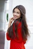 Jeune femme heureuse dans la robe rouge dans la perspective d'un bloc Photographie stock