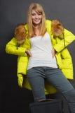 Jeune femme heureuse dans la veste chaude avec la valise Photos stock