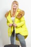 Jeune femme heureuse dans la veste chaude avec la valise Images stock