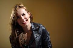 Jeune femme heureuse dans la veste en cuir noire sur le fond brun Images libres de droits