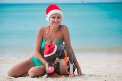 Jeune femme heureuse dans le chapeau de Noël se reposant à la plage avec son chien d'amstaff d'ami Photos stock